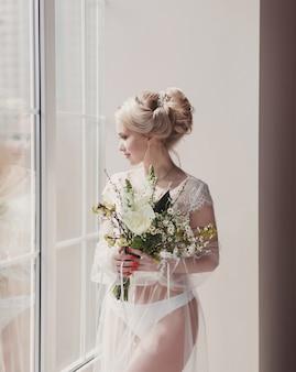 窓際のウェディングドレスで美しい金髪の花嫁。花嫁の朝