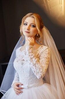 頭にベールを付けた白いウェディング ドレスを着た朝の美しい金髪の花嫁、結婚式前の花嫁のポートレート