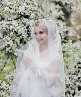 ウェディングドレスの美しい金髪の花嫁。公園の女性の肖像画。髪型の女性。屋外のかわいい女性