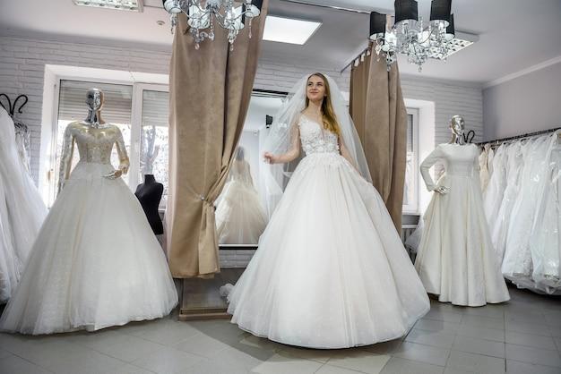 Красивая блондинка невеста позирует в свадебном платье