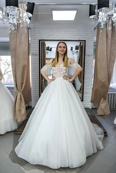 ウェディングドレスでポーズをとる美しいブロンドの花嫁