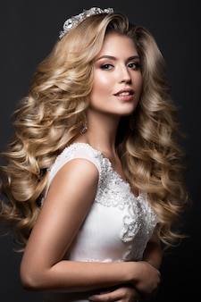 Beautiful blonde bride in wedding image with curls and crown. beauty face.
