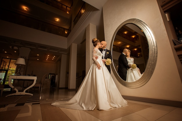 Beautiful blonde bride with bridegroom at the mirror in wedding suits
