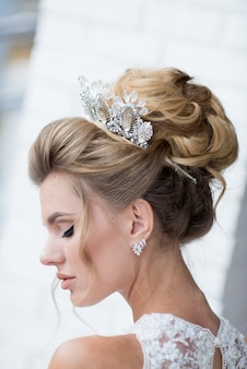 Beautiful blonde bride with high hair-do and precious silver wreath on her hair