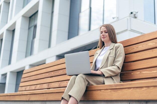 Красивая белокурая деловая женщина в куртке, работающая на ноутбуке, садится на скамейку на улице в городе