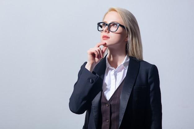 灰色の背景にスーツで美しい金髪女性実業家
