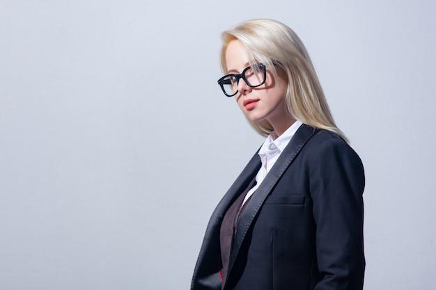 Красивая блондинка предприниматель в костюме на сером фоне