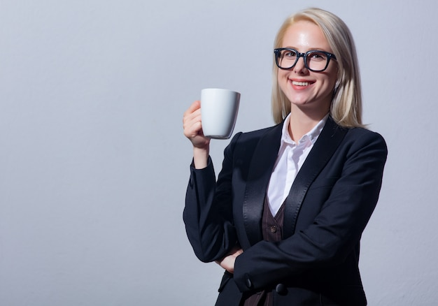 一杯のコーヒーとスーツを着た美しい金髪女性実業家