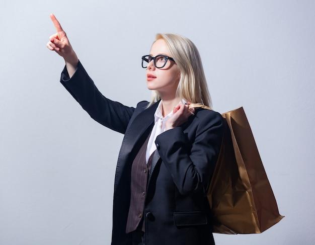 灰色の背景にショッピングバッグとスーツを着た美しい金髪女性実業家