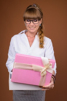 Beautiful blonde businesswoman with braided hair holding gift box
