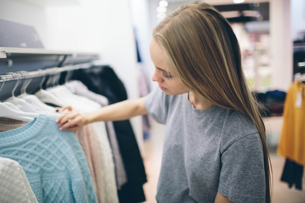 Beautiful blonde buys new things in a clothing store. seller works in a boutique