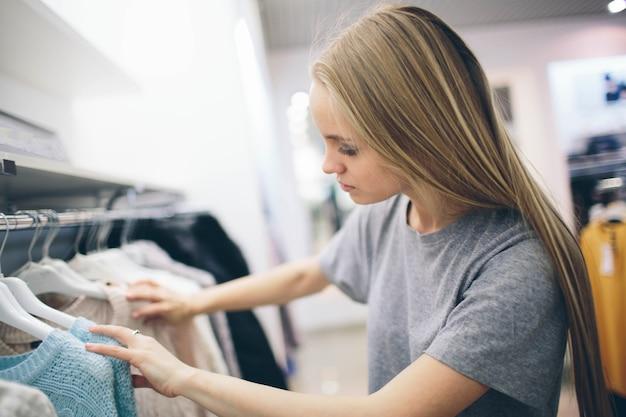 美しいブロンドは衣料品店で新しいものを買います。売り手はブティックで働いています