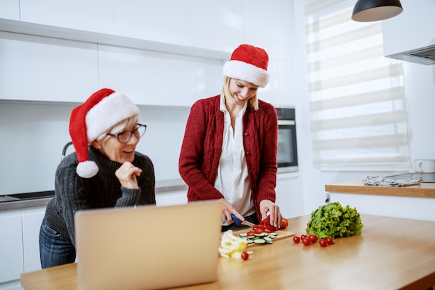Beautiful blonde caucasian pregnant woman preparing healthy food for christmas dinner. her mother standing next to her and looking at recipe on laptop. both having santa hats on heads. kitchen.