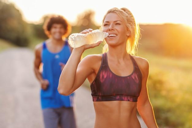 彼女のボーイフレンドが彼女の後ろを実行している間美しい金髪白人女性は水を飲む。