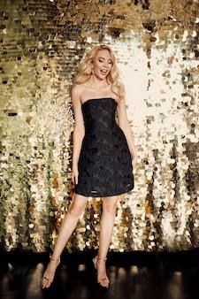 金色の背景のパーティーでリトルブラックドレスの美しい金髪白人女性