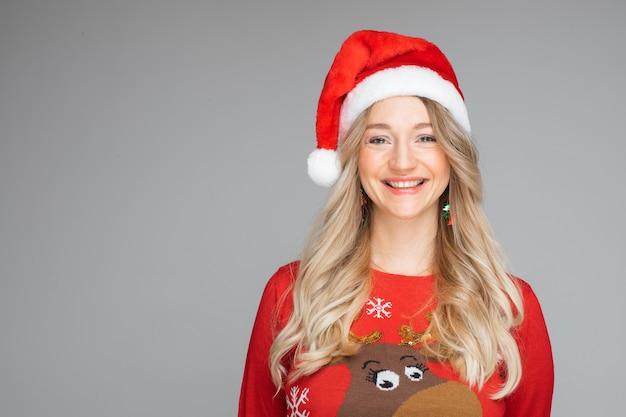 サンタの帽子をかぶった美しい金髪の白人女性。