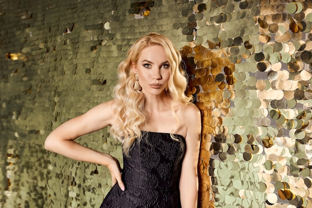 Beautiful blonde caucasian woman in little black dress on the party on golden background