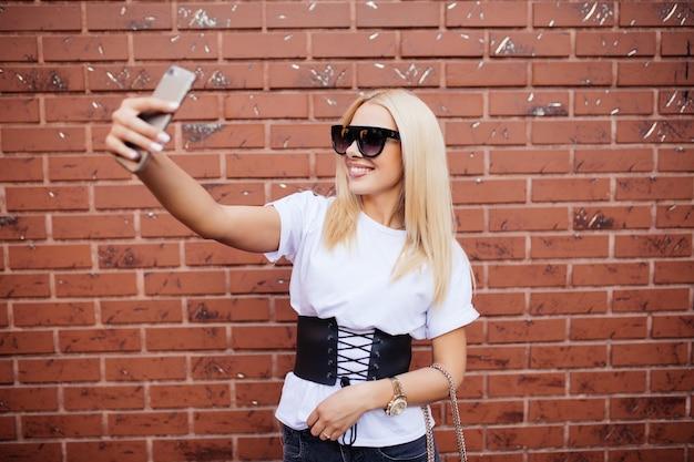 Bella bionda donna caucasica in piedi davanti al muro di mattoni e fare selfie.