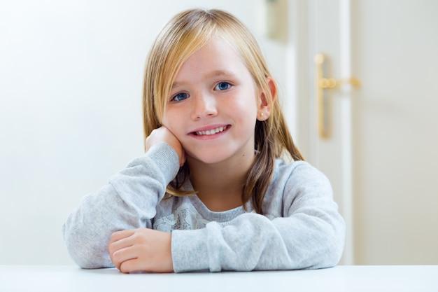 부엌에서 테이블에 앉아 아름 다운 금발 아이.