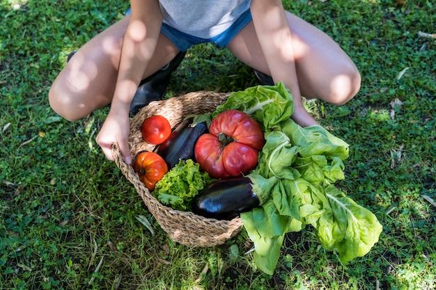 Beautiful blonde children holding vegetables basket