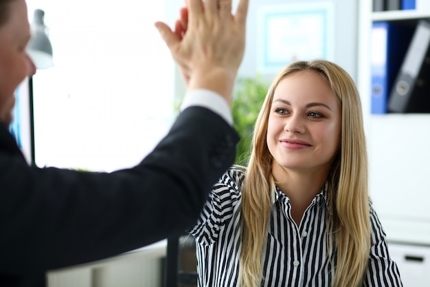 Beautiful blonde clerk giving high five to male customer