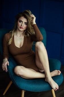아름 다운 금발 안락의 자에 그녀의 다리를 건너. 블루 룸에서 회색 안락의 자에 다른 포즈에 섹시 한 여자.
