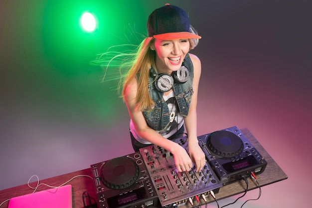 Beautiful blonde dj girl on decks on the party on the background of multicolored smoke