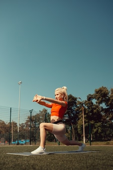 Beautiful blonde doing stretching on the lawn of a football field