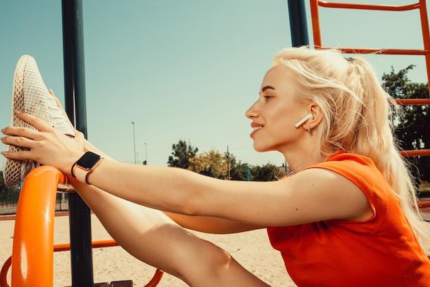 Красивая блондинка делает растяжку на детской площадке