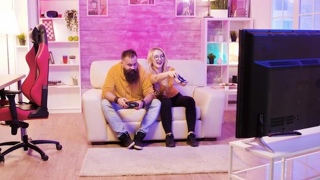 소파에 앉아 친구와 함께 온라인 비디오 게임을 하는 아름다운 금발 여성.