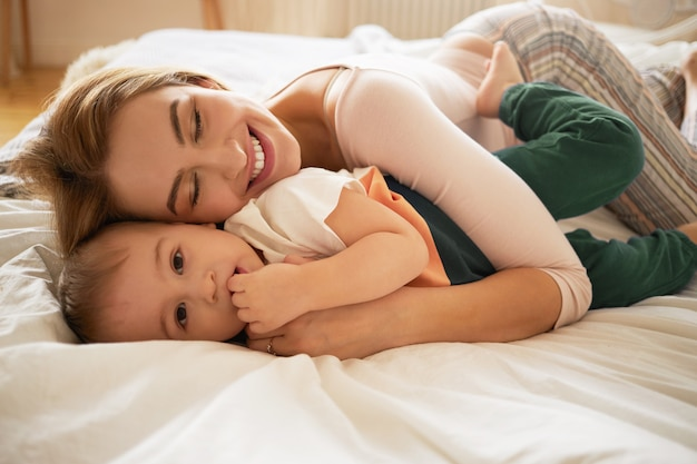 Beautiful blonde female smiling broadly lying on undone bed and embracing awakened toddler son. cozy sweet shot of cute mom and little child bonding in bedroom. family, love, care and affection