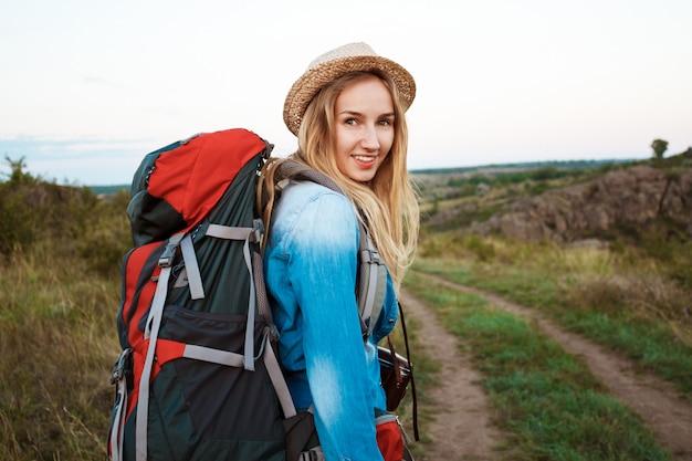 Beautiful blonde female traveler with backpack smiling, canyon background