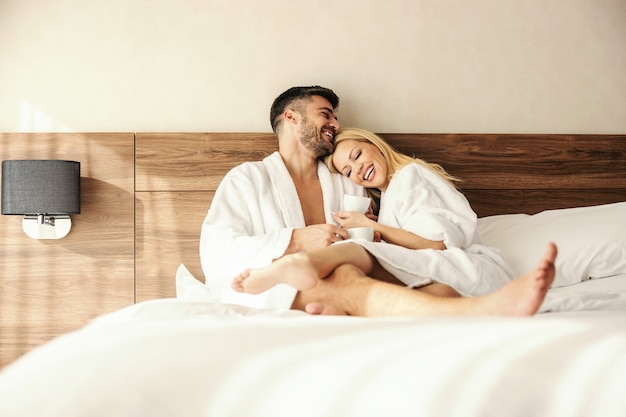 Beautiful blonde gently rests her head on the man's shoulder while they both hold a cup of coffee in bathrobes