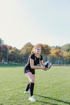 Beautiful blonde girl catching a rugby ball