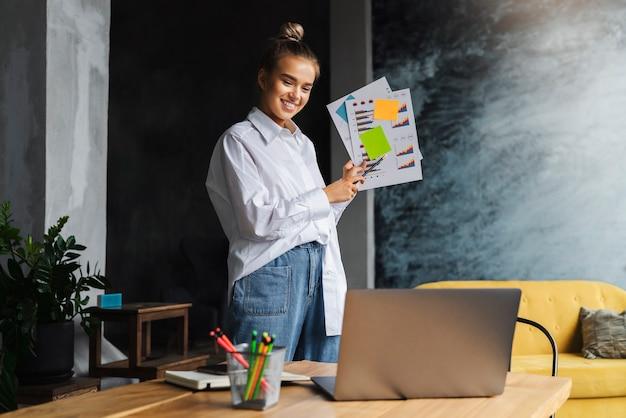 아름다운 금발 소녀 컨설턴트는 노트북을 사용하는 온라인 회의를 통해 회사의 비즈니스 분석을 수행합니다.