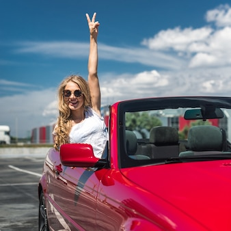 Beautiful blonde girl in a convertible red car. sunny day