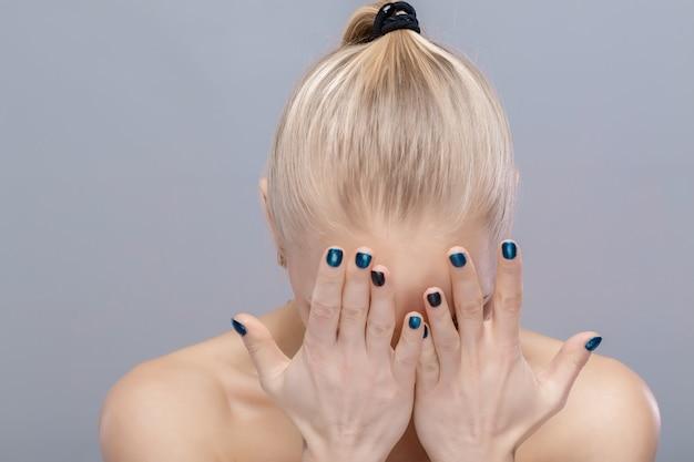 아름 다운 금발 소녀는 그녀의 손으로 그녀의 얼굴을 가립니다. 절망