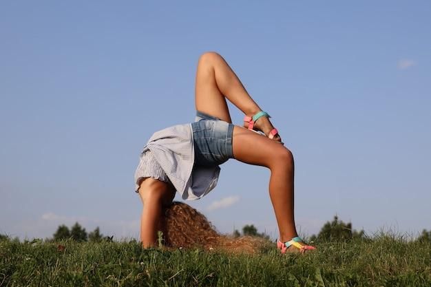 Красивая блондинка делает гимнастические упражнения мост на природе. фото высокого качества