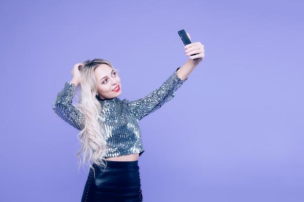Beautiful blonde girl doing selfie, isolate on blue