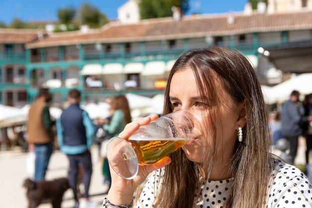 전형적인 마을 광장에서 맥주를 마시는 아름 다운 금발 소녀