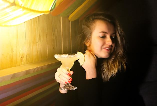 Красивая белокурая девушка пьет коктейль маргарита в кафе. стильная женщина в черном свитере расслабляющий в баре. уютная атмосфера. романтические огни.
