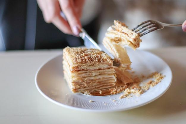 Beautiful blonde girl enjoying dessert in coffee shop, food blogger