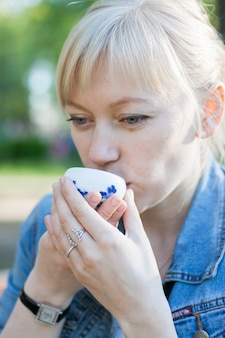 Beautiful blonde girl enjoys drinking tea from a small bowl on the street