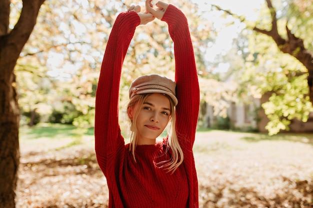 美しいブロンドの女の子は秋の公園で幸せを感じます。葉の間でポーズをとる赤いセーターの素敵なyounf女性。
