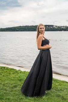검은색 우아한 세련된 드레스를 입은 아름다운 금발 소녀는 호수 근처에 서서 휴식을 취하고 생활 방식을 취합니다.