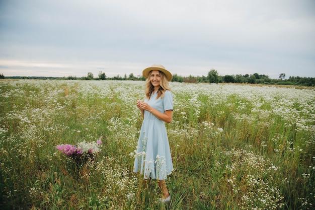ヒナギクの分野で美しいブロンドの女の子。花のフィールドに青いドレスの女。ヒナギクの花束を持つ少女。村の夏の入札写真。野の花。麦わら帽子の少女