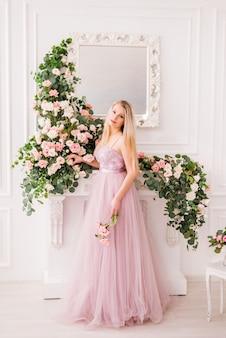포즈를 취하는 꽃의 긴 부드러운 보라색 드레스에 아름 다운 금발 소녀. 향수, 패션 및 뷰티의 개념