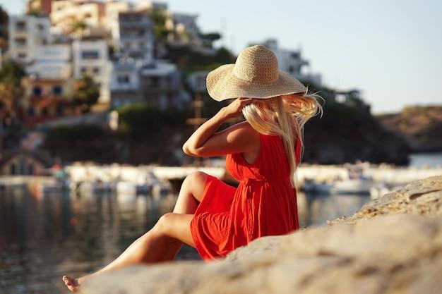 밀짚 모자에 아름다운 금발 소녀는 마을을 향해 찾고 바위의 가장자리에 앉아