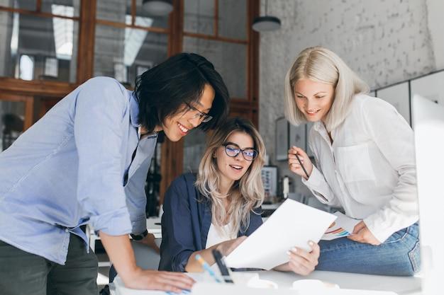 彼女のテーブルの横に立っているアジアの同僚へのレポートを示す眼鏡の美しいブロンドの女の子