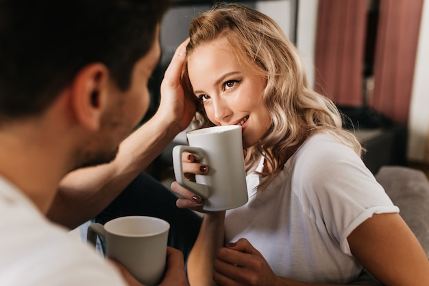 그녀의 남자 친구를보고 컵에서 커피를 마시는 사랑에 아름 다운 금발 소녀. 집에서 로맨틱 커플의 부드러운 귀여운 초상화.